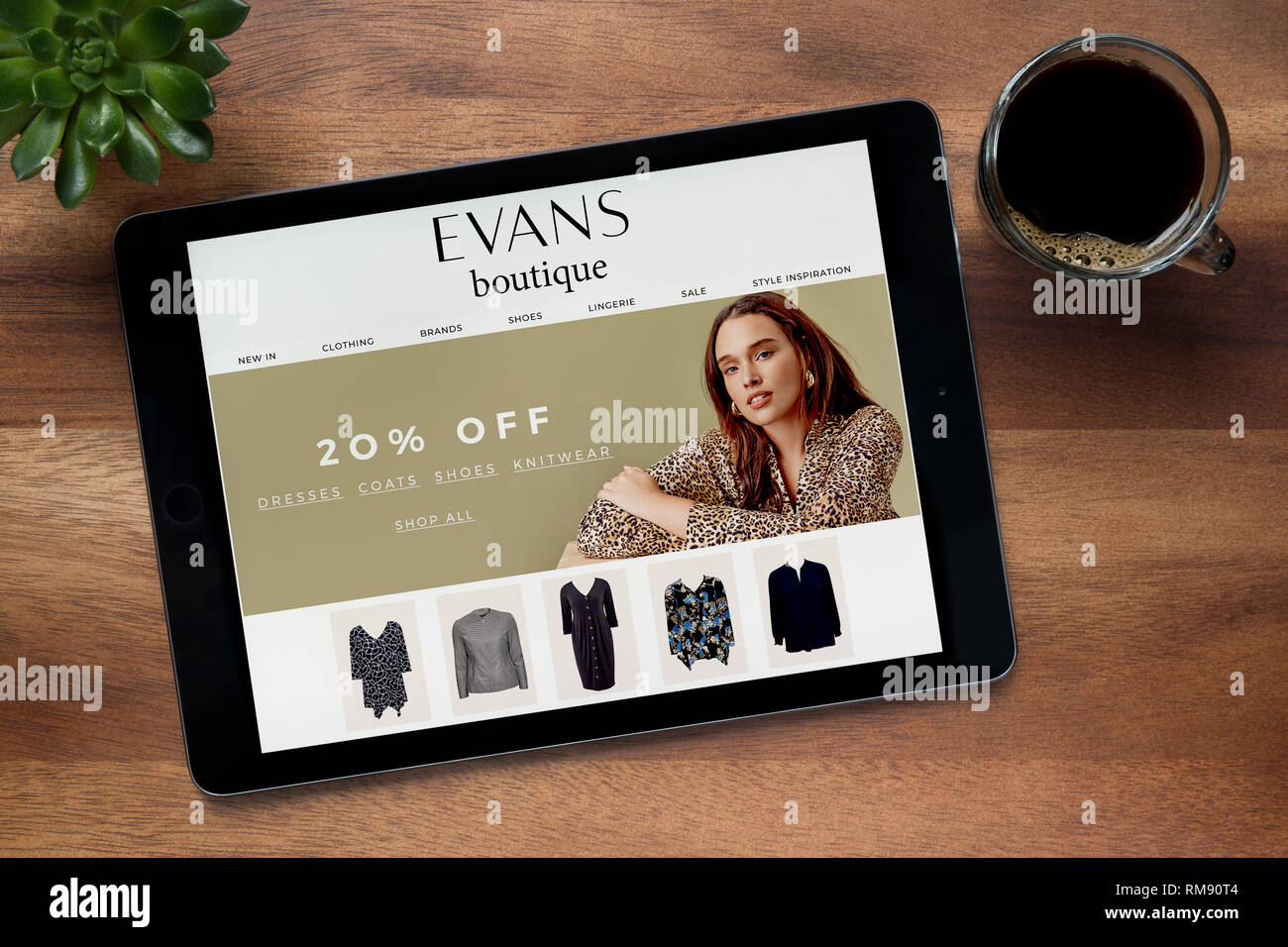 The website of Evans Boutique is seen on an iPad tablet, on a wooden table along with an espresso coffee and a house plant (Editorial use only). - Stock Image