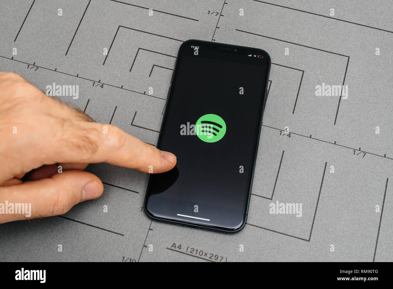 PARIS, FRANCE - NOV 9, 2017: Man POV personal perspective on the latest iPhone X XS with hand pressing the Spotify button - Stock Image