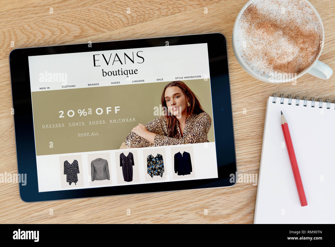 The Evans Boutique website features on an iPad tablet device which rests on a wooden table beside a notepad (Editorial use only). - Stock Image
