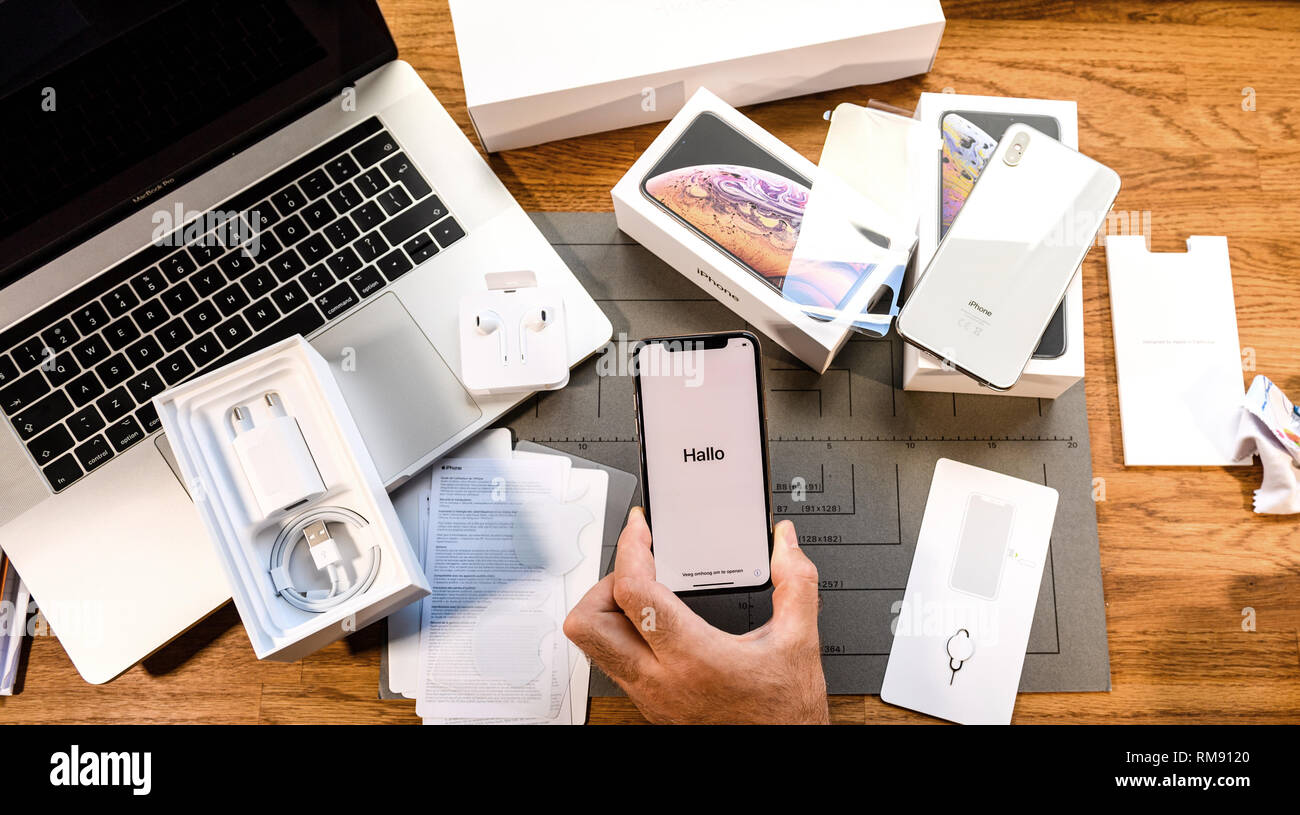 PARIS, FRANCE - SEPT 24, 2018: man first run onf Apple iphone XS and XS Max with Hallo german message during setup - Stock Image