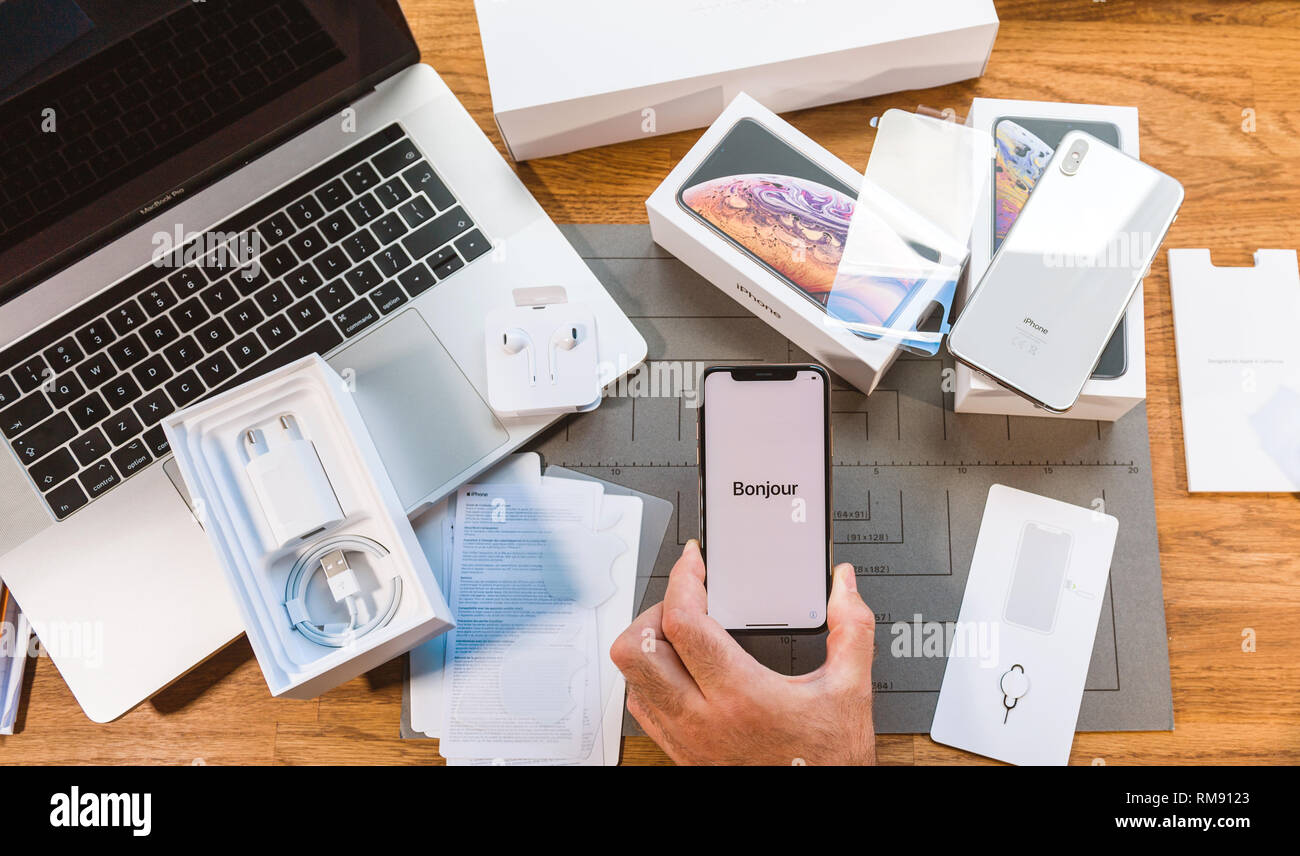 PARIS, FRANCE - SEPT 24, 2018: Curious man POV unboxing two iphone XS and Apple Watch series 4 on wooden table next to MacBook Pro laptop Bonjour Hello message during first run - Stock Image