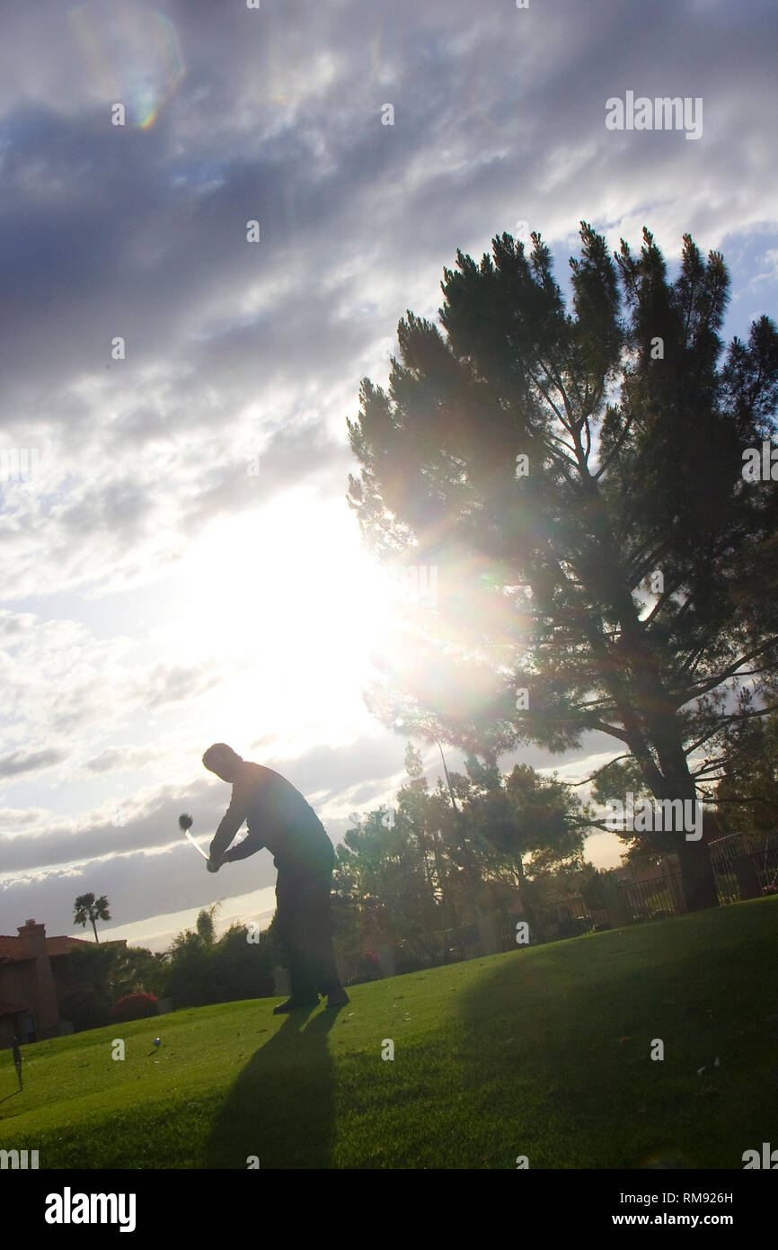 A silhouette of a golfer chipping the ball off the fairway. - Stock Image