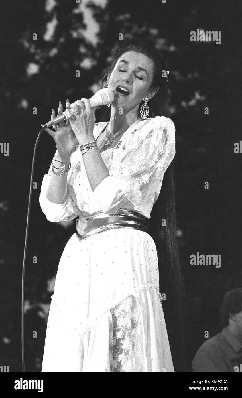 Country singer Crystal Gayle is shown singing on stage during a 'live' concert appearance. - Stock Image