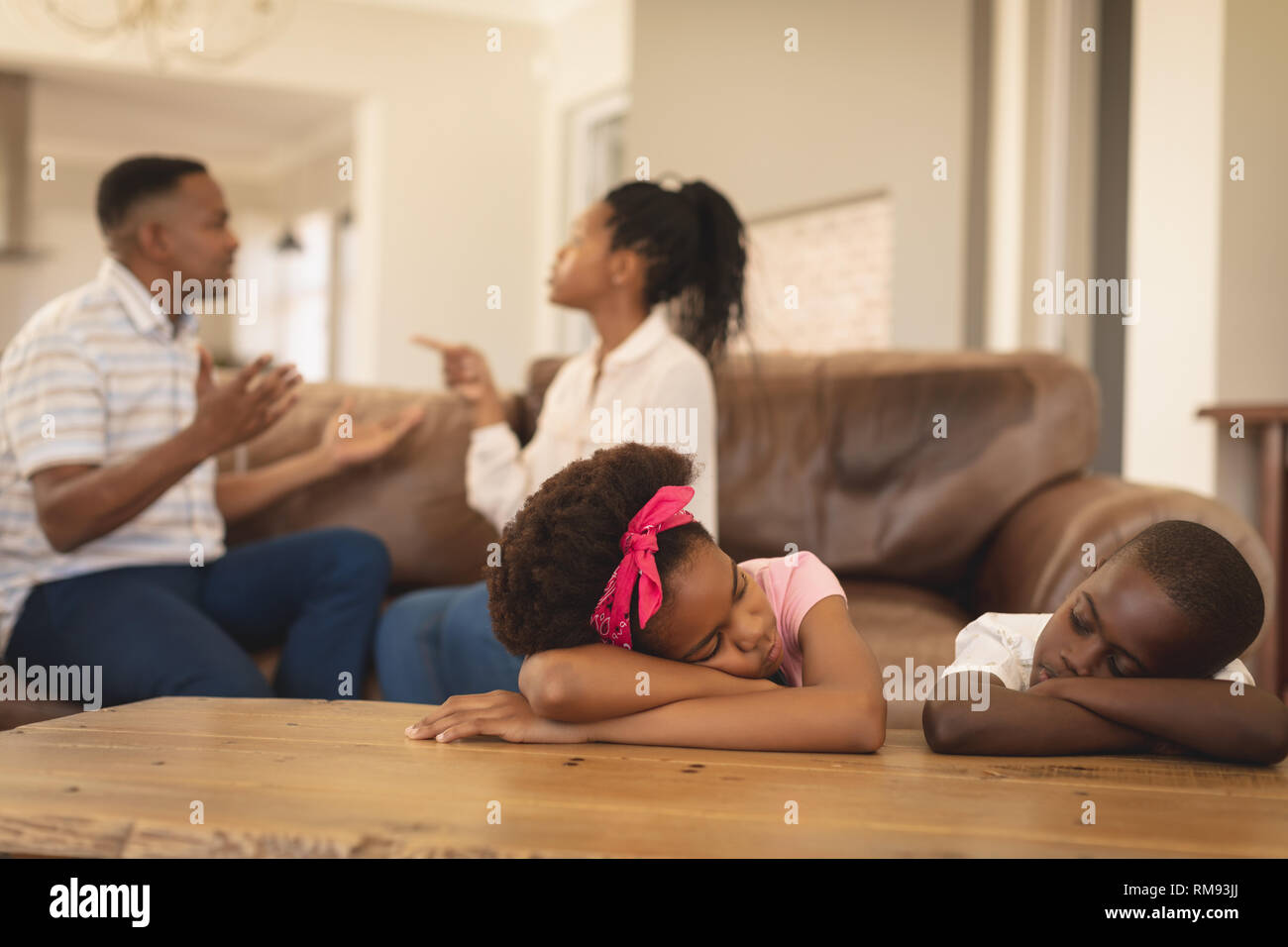 African American children leaning on table while parents arguing on the sofa Stock Photo