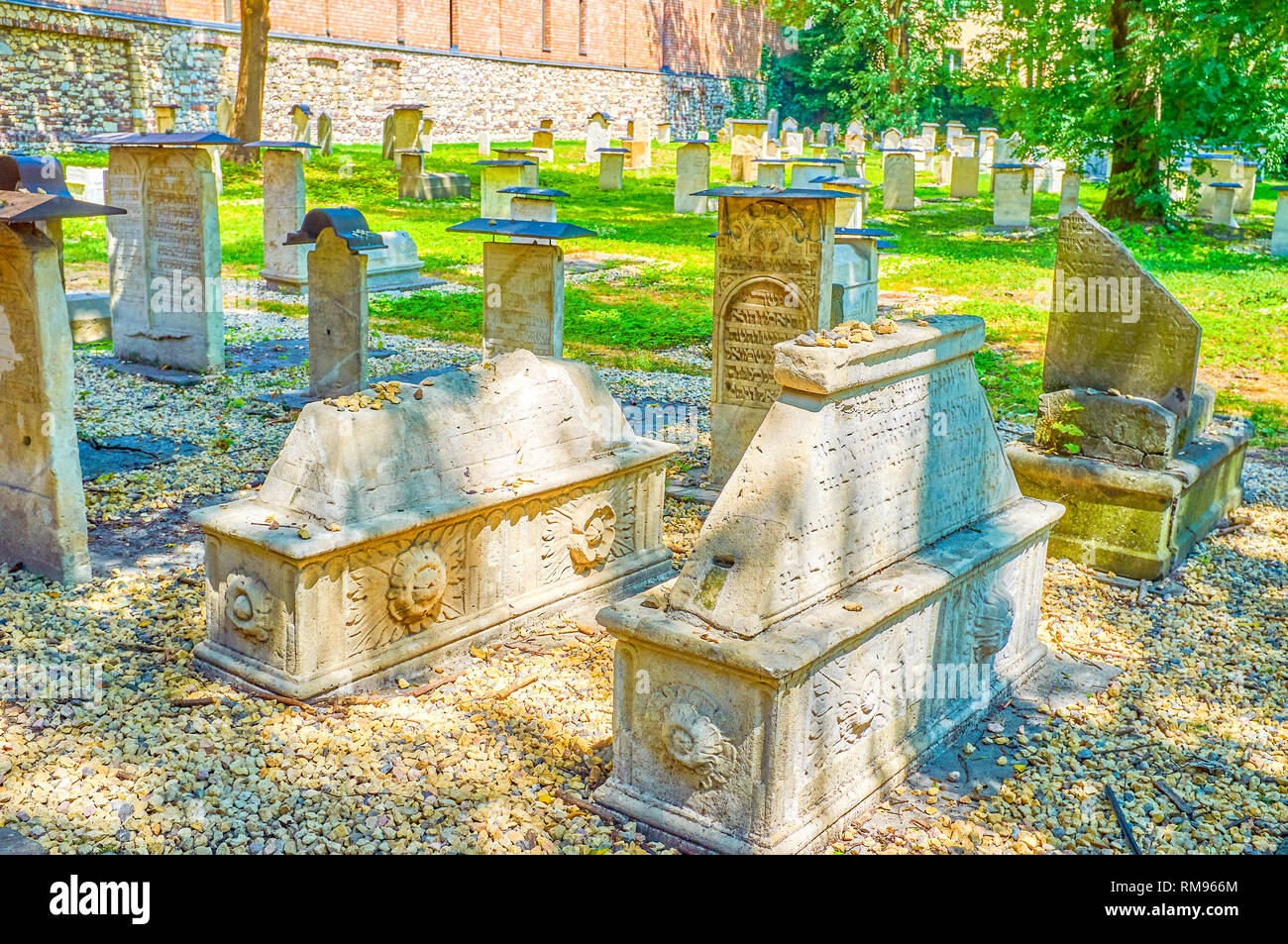KRAKOW, POLAND - JUNE 21, 2018: The carved tombstones with inscriptions in old Jewish language of historical Remah Cemetery in the center of Kazimierz - Stock Image