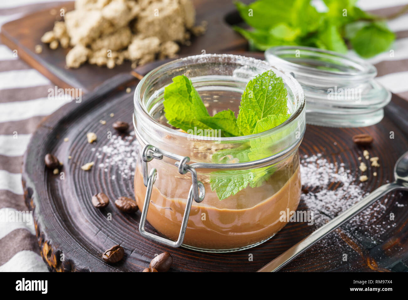Chocolate pudding with fresh mint in a jar. Healthy vegan dessert concept. - Stock Image
