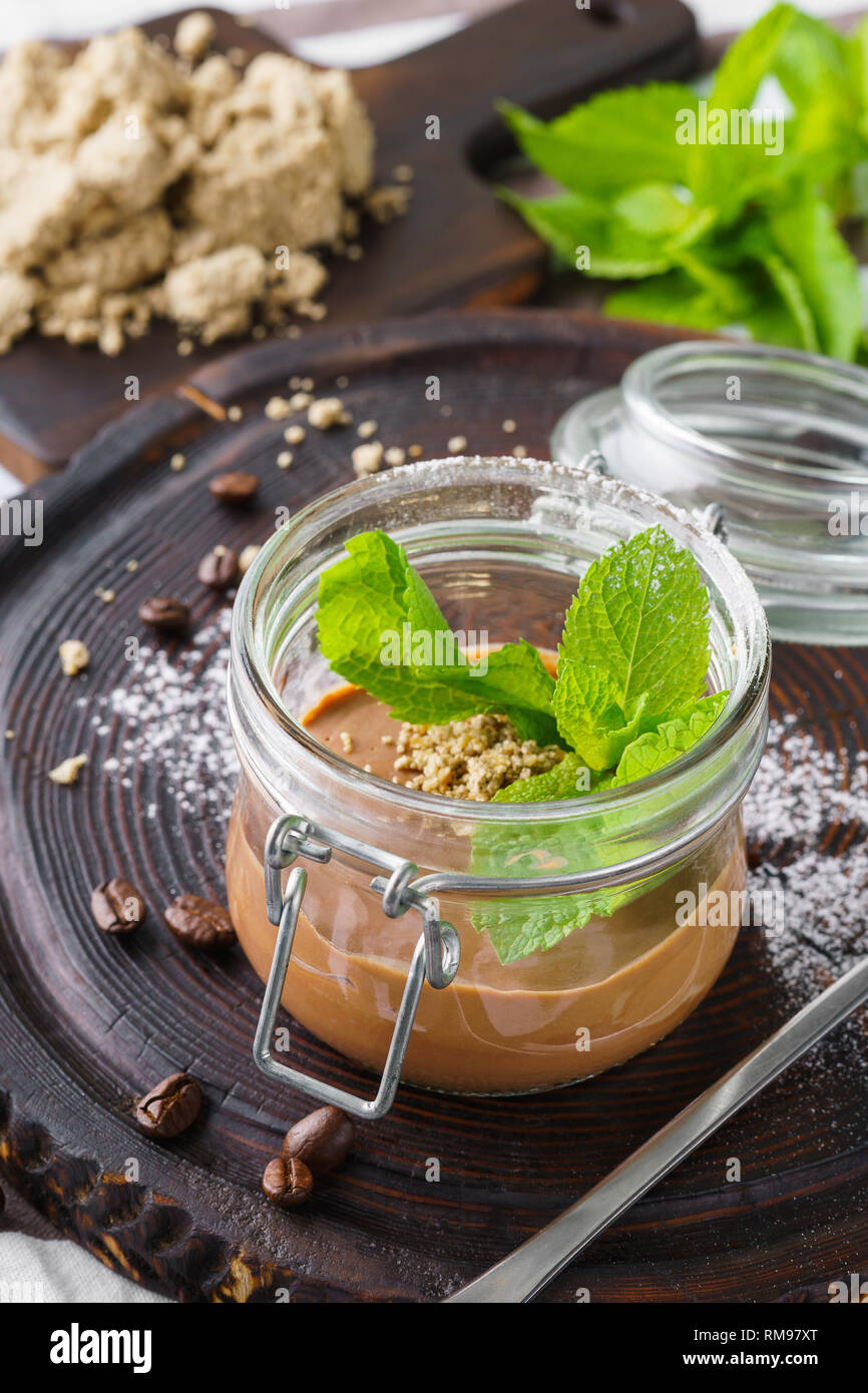 Vegan chocolate mousse with halvah and fresh mint in a jar for dessert.. - Stock Image