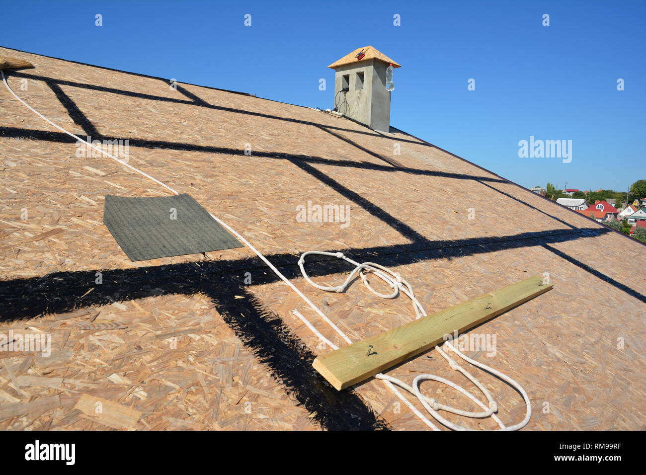 Roofing preparation asphalt shingles installing on house construction wooden roof with bitumen spray and  protection rope, safety kit. Roofing constru - Stock Image