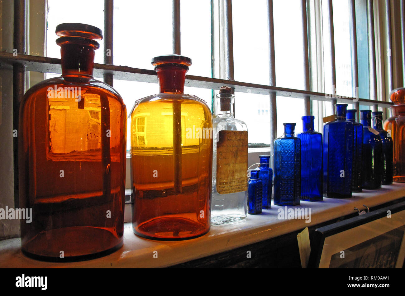 Coloured Victorian medicine bottles on a shelf, blue, orange, yellow glass - Stock Image
