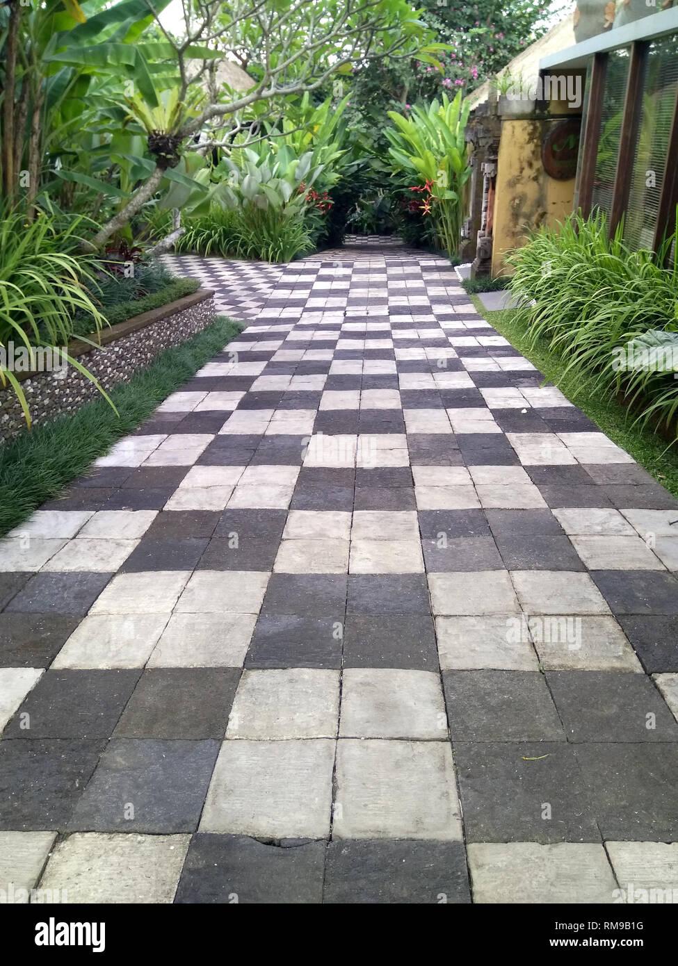 Ubud-Green entranced chess styled paved path - Stock Image