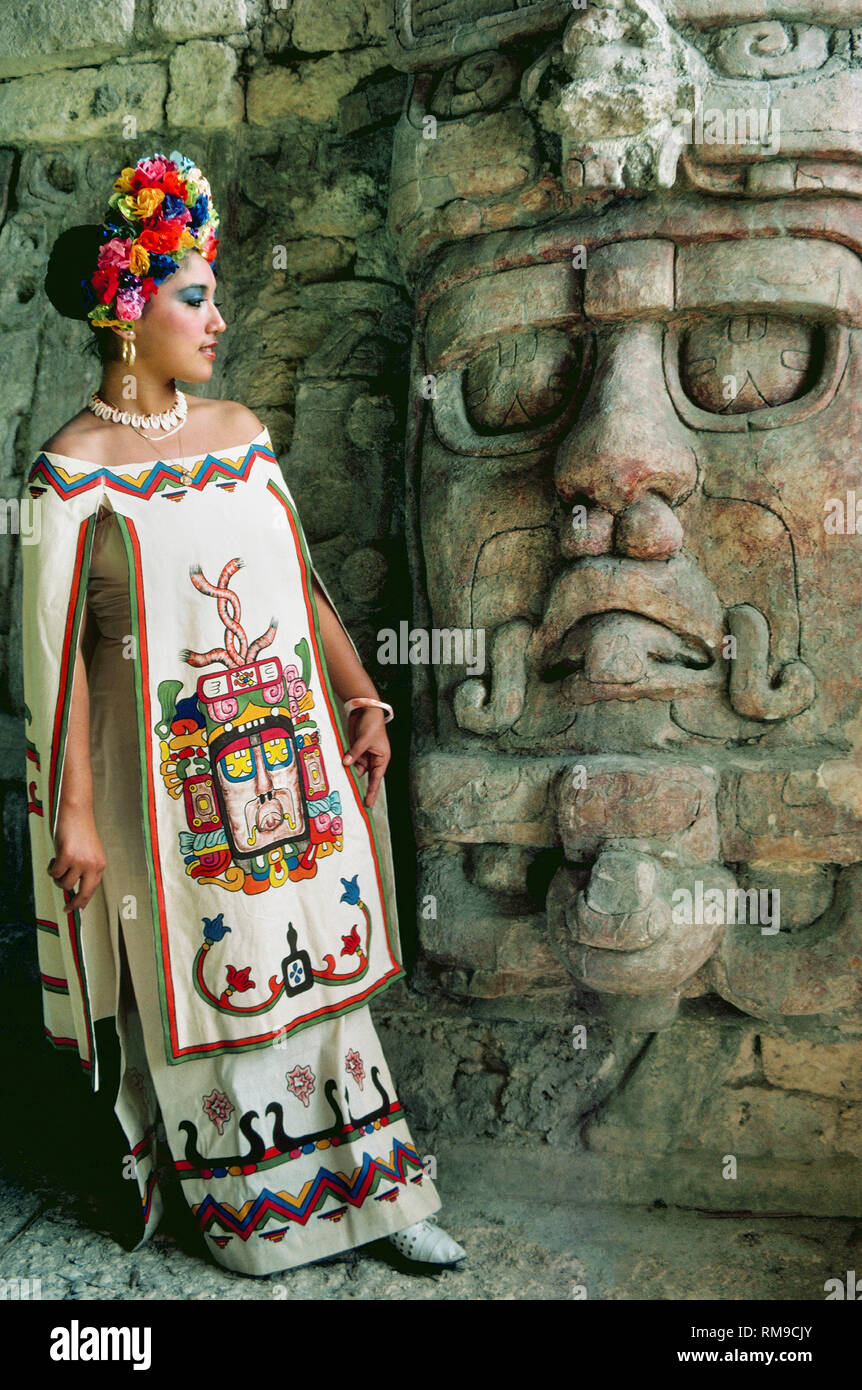 A woman poses next to one of five well-preserved stucco masks honoring the Mayan sun god Kin'ich Ahau at Kohunlich, an archaeological site on the Yucatán Peninsula in the state of Quintana Roo, Mexico. The contemporary design of her Mayan dress portrays the 6- to 8-feet-tall (1.8 to 2.4 meters) sculpted masks that flank the central stairway of a 6th-Century pyramid called the Temple of the Masks. - Stock Image