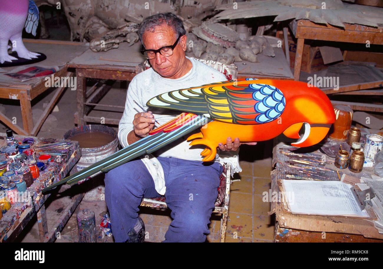 A male artisan carefully paints a colorful papier-mache bird