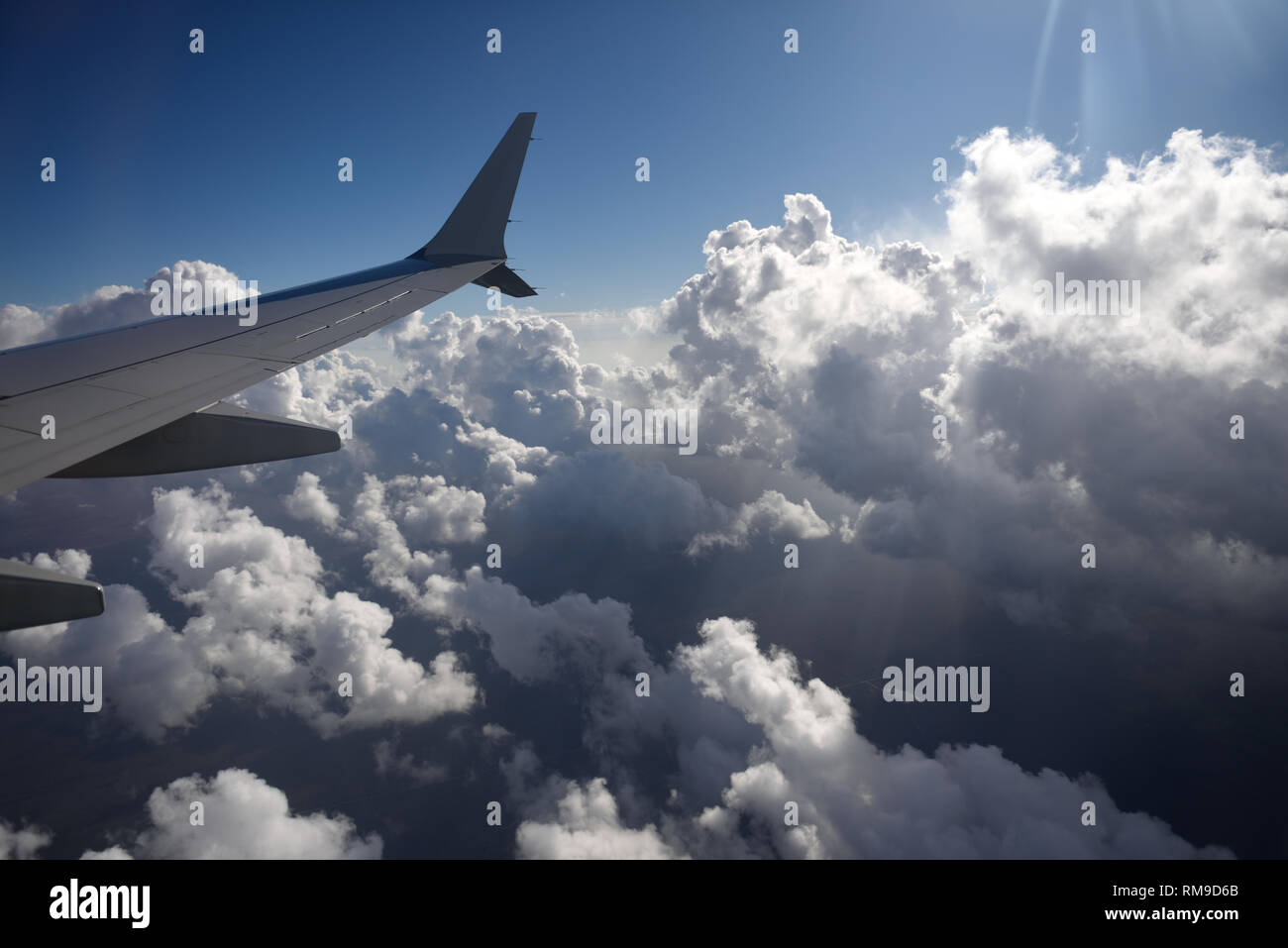 High altitude jet airplane view of wing with winglet, flying above clouds. - Stock Image