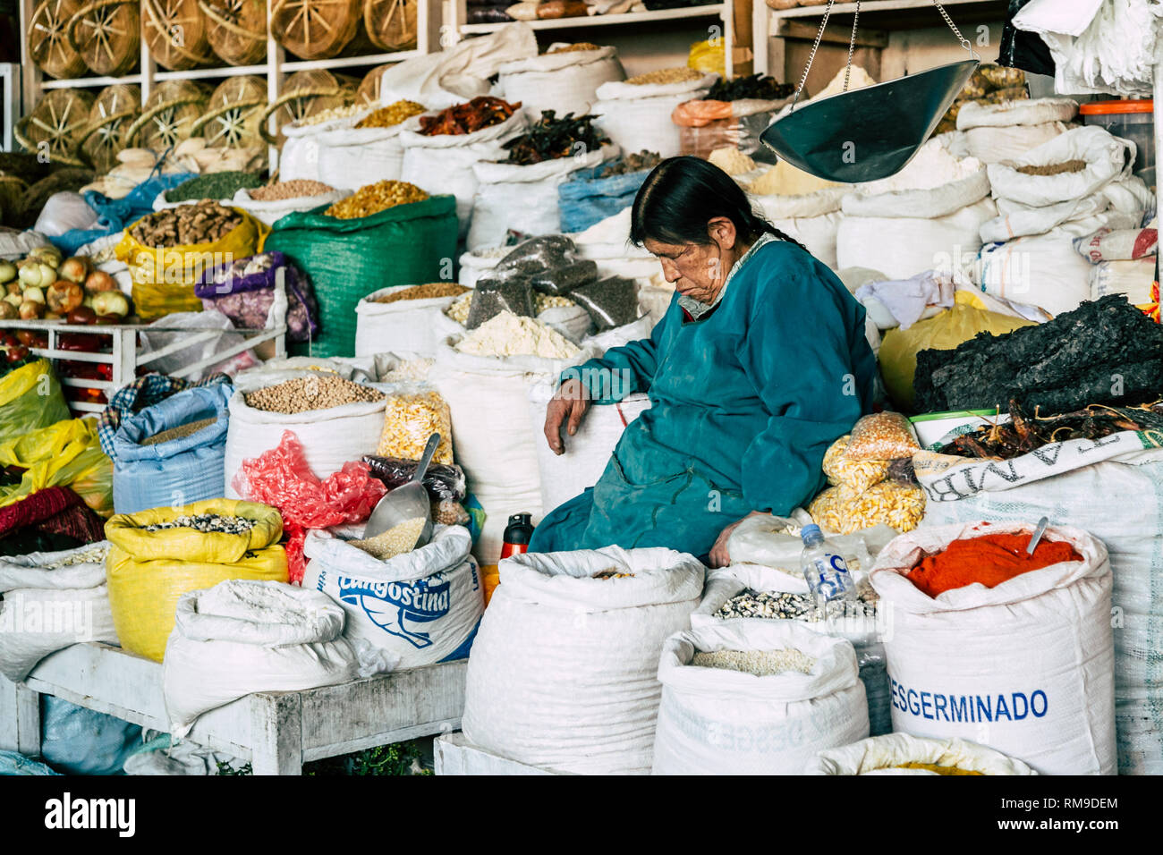 An elderly Peruvian woman sleeping sitting amongst sacks of grains and other produce that she is selling in the local market of Cusco, Peru. - Stock Image