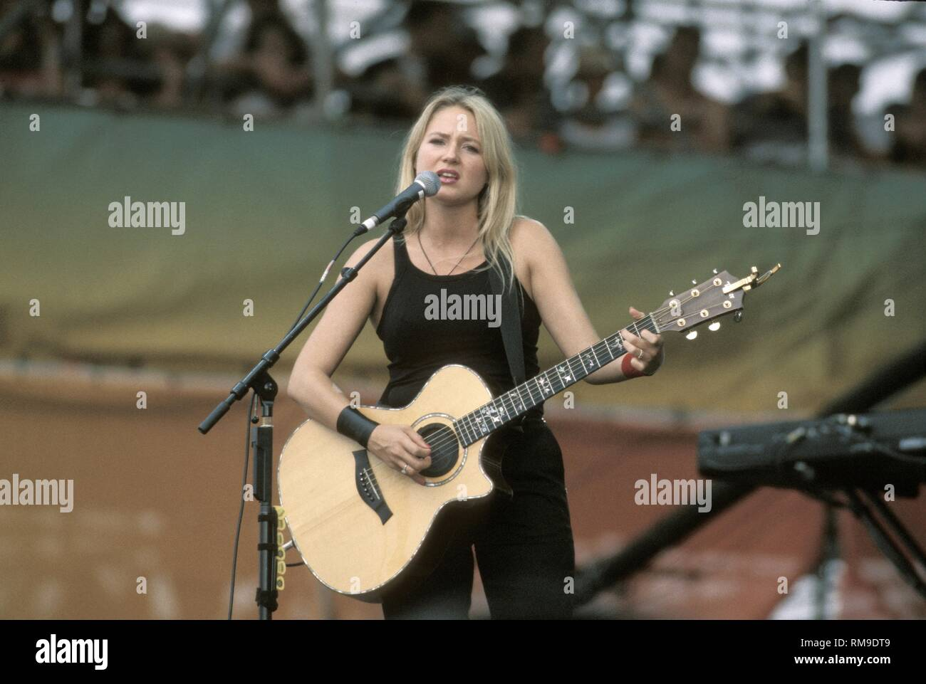Jewel is shown performing on stage during her concert performance at woodstock '99. - Stock Image