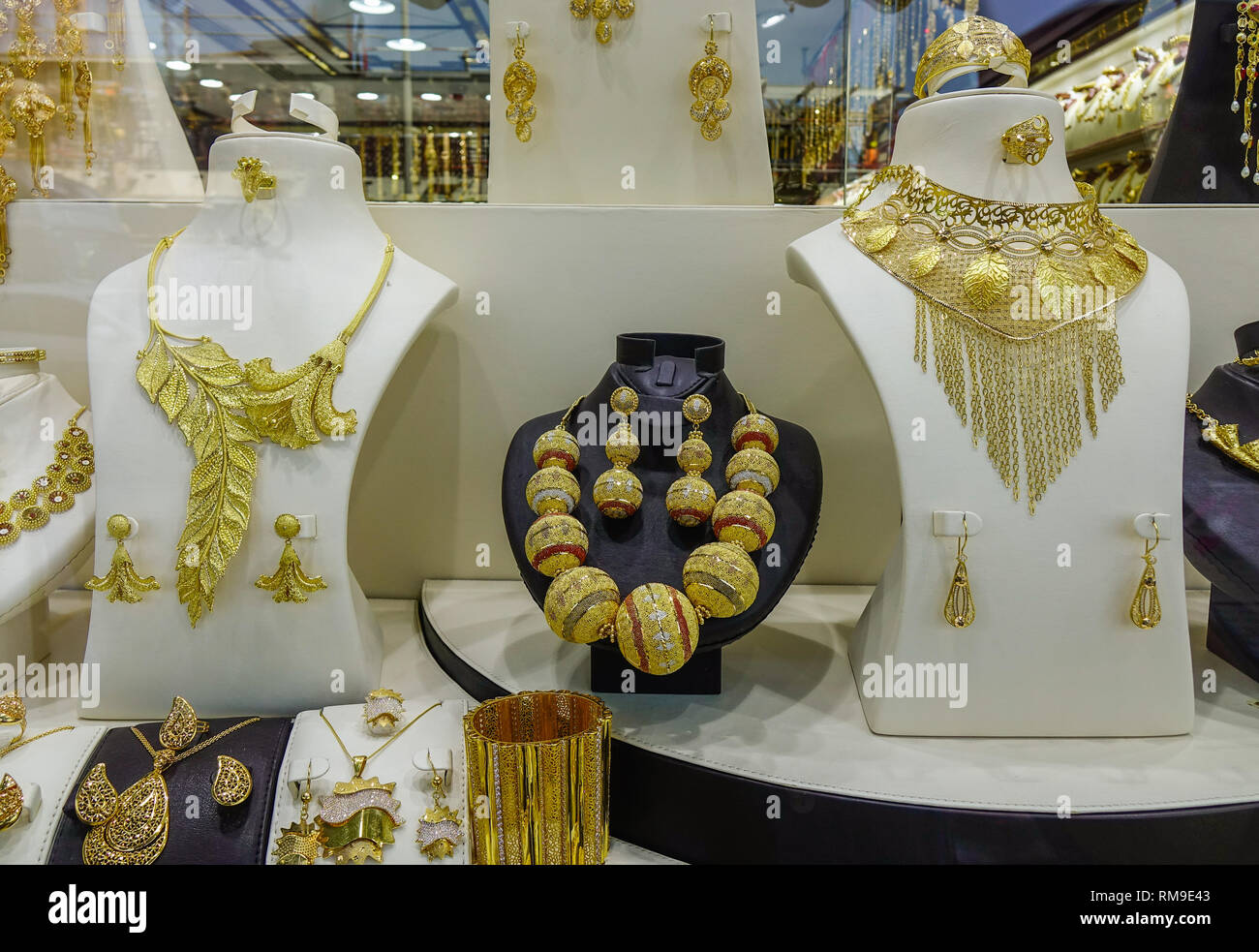 Dubai, UAE - Dec 6, 2018. Gold jewelry in the display window of a jewelleries shop in Dubai Gold Bazaar (Souk). - Stock Image