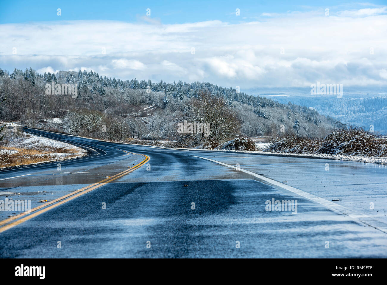 Winter landscape with wet melting road and hills with snow-covered trees, meadows and road shoulders and mountains hidden in the hanging clouds in the Stock Photo