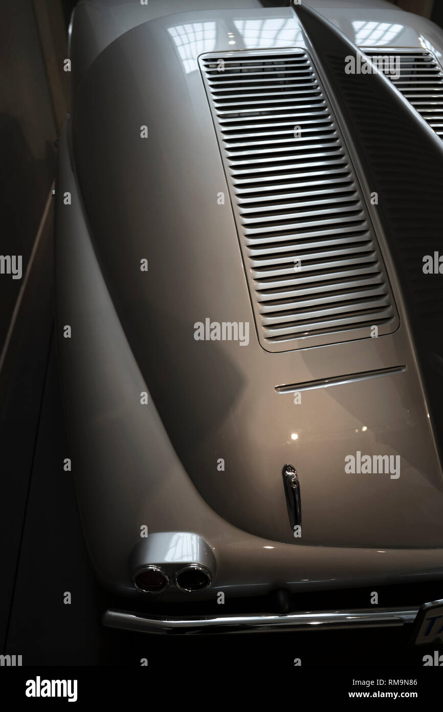 Old vintage car with a streamlined aerodynamic body shape with large fenders and convex lights inherent in the design of retro cars, and with geometri - Stock Image