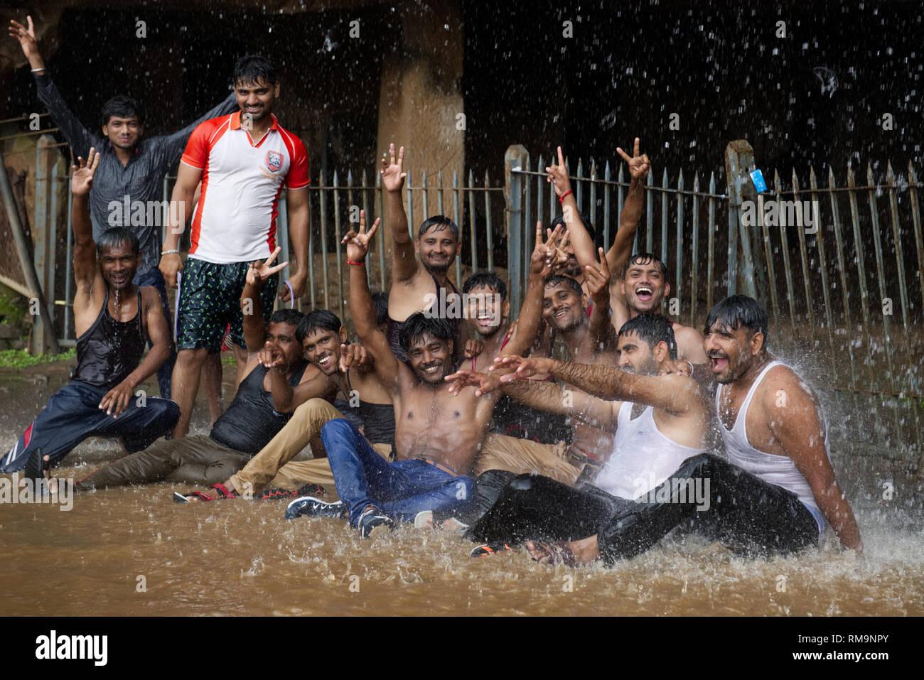 A joyous group enjoying Monsoon rainfall. Celebrating the climate of Mumbai. - Stock Image