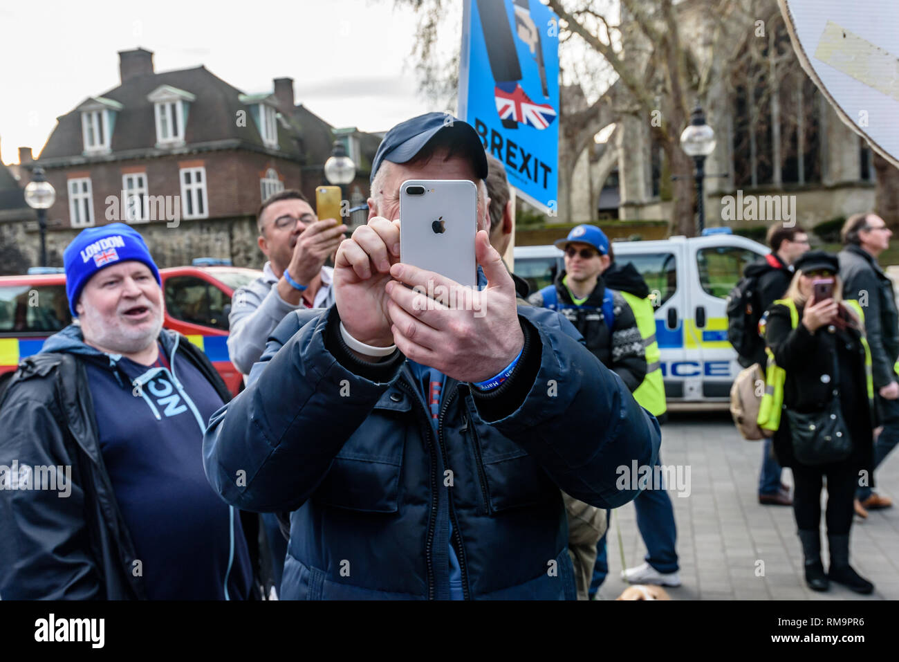 London, UK. 13th February 2019. One of the small group of extreme right Breixteers who come to harass Steven Bray and SODEM by following them around, shouting at them and recording video turns his phone camera to video me taking photographs. They complain at the police who try to keep the two groups apart accusing them of showing favouritsm by protecting the protesters.  Peter Marshall/Alamy Live News - Stock Image