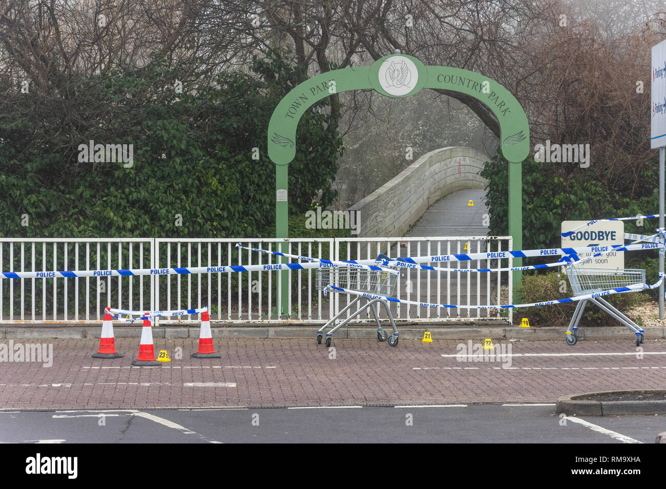 Trowbridge, Wiltshire, UK. 14th February 2019. Overnight there was a double stabbing near the Tesco Extra store. One victim rumoured to be critical. View of the Bridge into the Country park with crime scene markers leading over the bridge Credit: Starsphinx/Alamy Live News Stock Photo