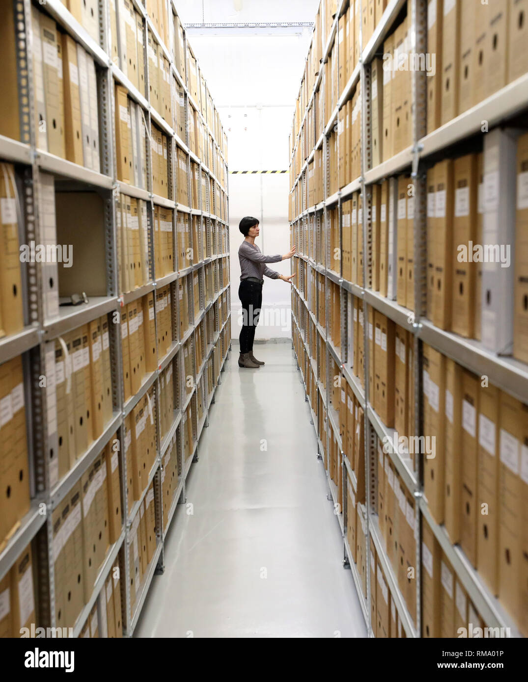 """Neubrandenburg, Germany. 05th Feb, 2019. Heike Thieme, head of the archive in the Neubrandenburg branch of the authority of the Federal Commissioner for Stasi Files (BStU), is on her way through the archive. In a monthly series of events, the Neubrandenburg branch office of the BStU provides information on """"Rapport-Berichte"""" from the period of upheaval. Before each reading there is a guided tour through the archive. Credit: Bernd Wüstneck/dpa-Zentralbild/ZB/dpa/Alamy Live News Stock Photo"""