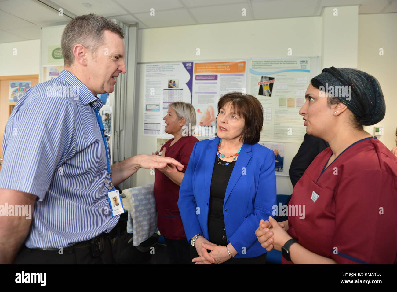 Kilmarnock, UK. 14 February 2019.(L-R) (L-R) Calum Morrison - Consultant Paedrician, Associate Medical Director Women Children & Diagnostics NHS Ayrshire and Arran; Health Secretary - Jeane Freeman; Attica Wheeler - Head of Midwifery Associate Nurse Director, NHS Ayrshire and Arran. Transforming maternity and neonatal care across Scotland Cabinet Secretary for Health Jeane Freemanl visits Crosshouse Hospital in NHS Ayrshire and Arran to announce a £12 million investment which will ensure mums, babies and other family members are all supported from pregnancy to birth and after. This includes - Stock Image