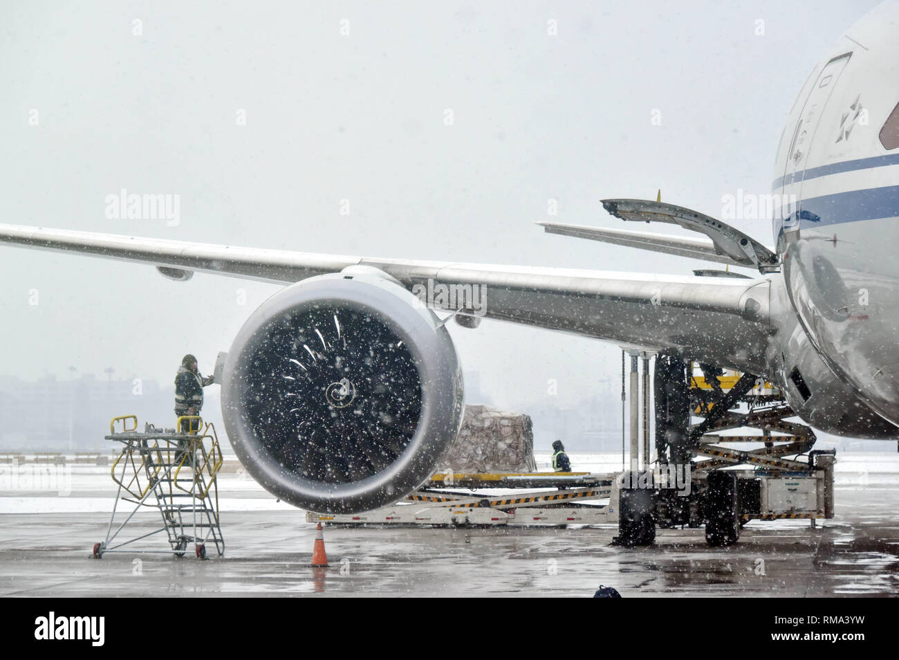 Beijing, China. 14th Feb, 2019. A staff member works during a preflight check in snow at the Beijing Capital International Airport in Beijing, capital of China, Feb. 14, 2019. Some flights of the airport were delayed or cancelled due to the snowfall on Thursday. Credit: Xinhua/Alamy Live News - Stock Image