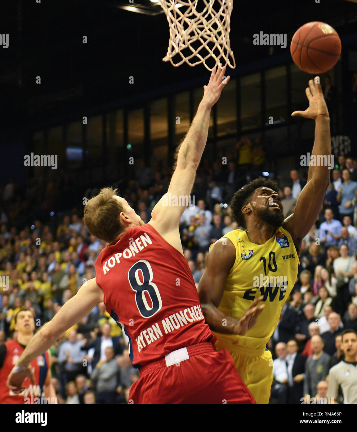 14 February 2019, Lower Saxony, Oldenburg: Basketball: Bundesliga, EWE Baskets Oldenburg - FC Bayern Munich, main round, 21st matchday. Oldenburg's Frantz Massenat (r) throws a basket at Munich's Petteri Koponen. Photo: Carmen Jaspersen/dpa - Stock Image
