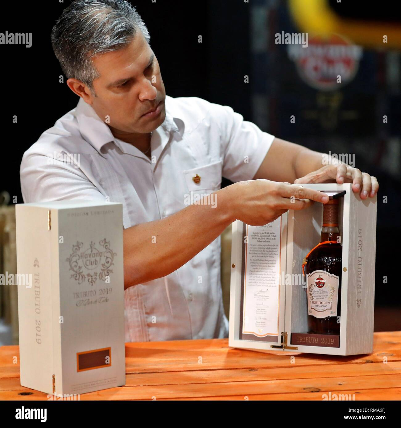 Havana, Cuba. 14th Feb, 2019. A barman opens a box of 'Tributo 2019', one of the luxury rums of Cuban rum company Havana Club, in Havana, Cuba, 14 February 2019. The company discarded that the reactivation of the 3rd title of the Helms Burton Act by the US can prejudice their activities. Credit: Ernesto Mastrascusa/EFE/Alamy Live News - Stock Image