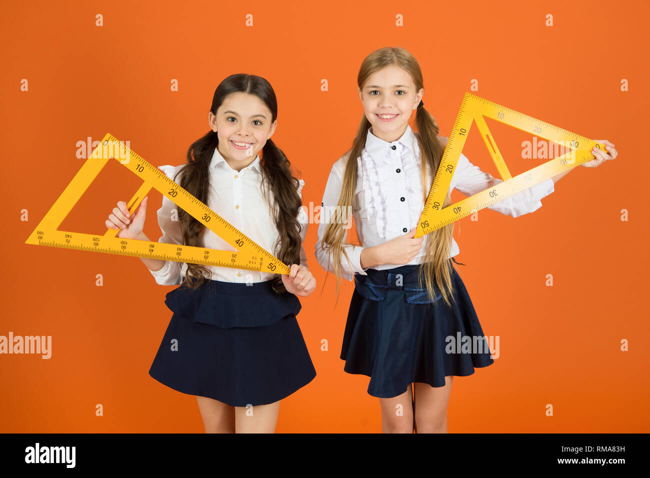 Education and school concept. School students learning geometry. Kids school uniform on orange background. Pupil cute girls with big rulers. Geometry school subject. Drawing with ruler chalkboard. - Stock Image