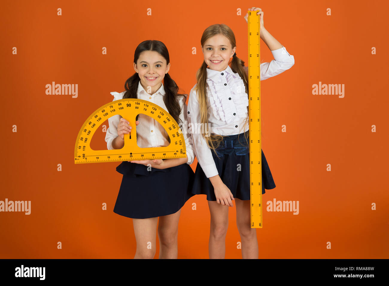 Pupil cute girls with big rulers. Geometry favorite subject. Education and school concept. School students learning geometry. Kids school uniform on orange background. STEM school disciplines. - Stock Image