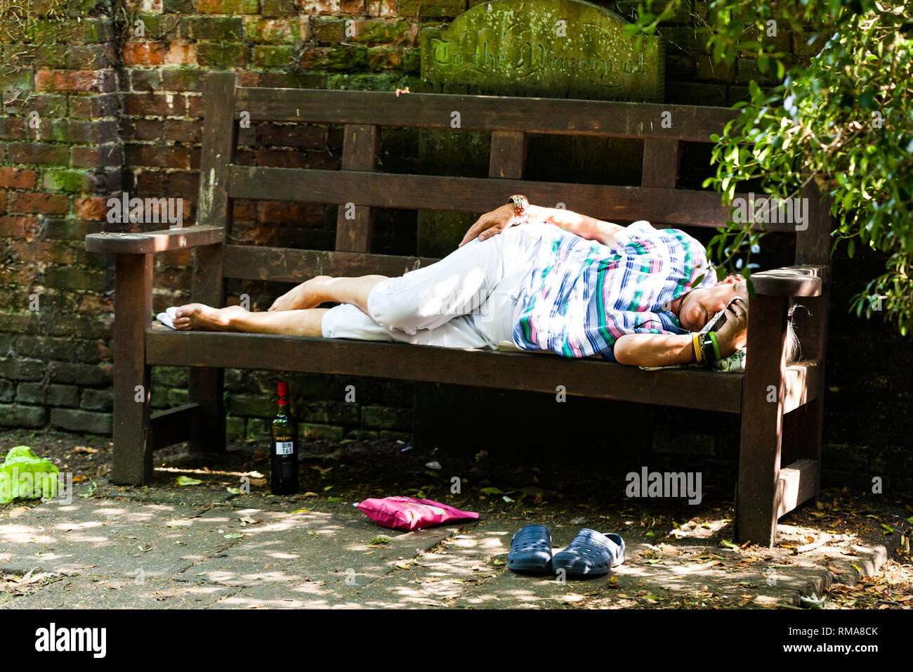 BIRMINGHAM, UK - March 2018 Elderly Drunk Woman Sleeping on Wooden Bench on Sunny Day. Bottle of Spirited Drink under the Seat. Pouch and Shoes on Dir Stock Photo