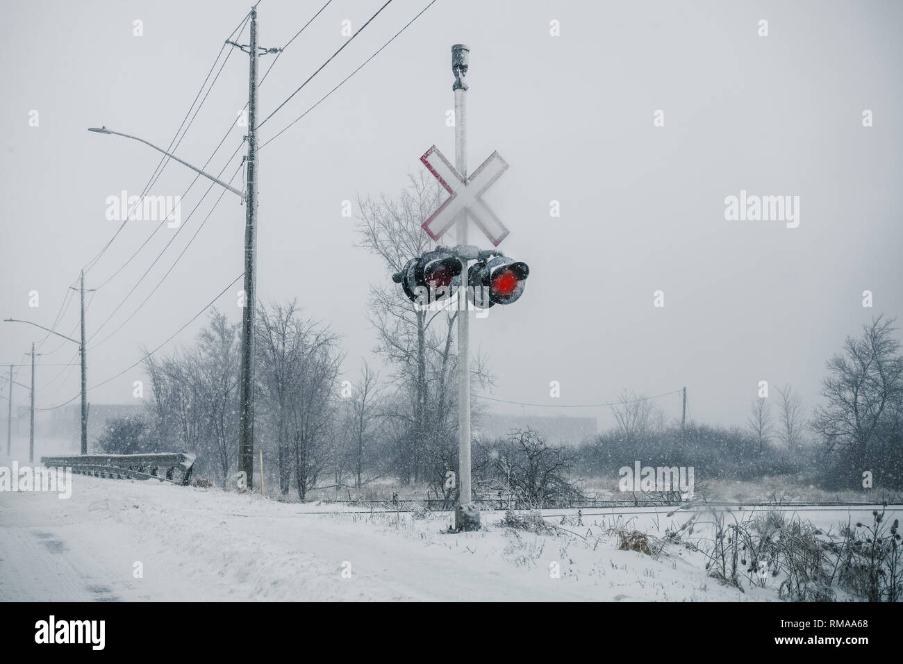 Winter, crossing railway sign and lights. - Stock Image