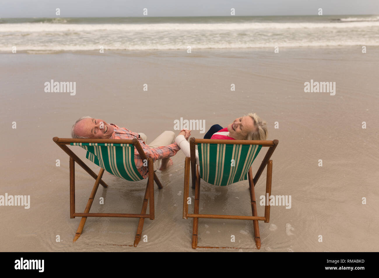 Happy senior couple holding hands of each other at the beach with ocean in the backgrou - Stock Image