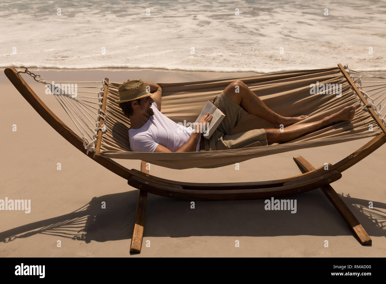 Young man with hat reading a book while relaxing on hammock at beach Stock Photo