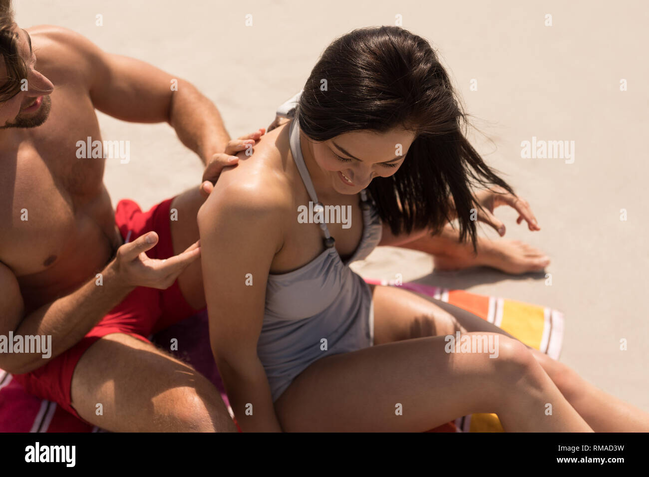 Happy young man applying sunscreen lotion on woman back at beach - Stock Image