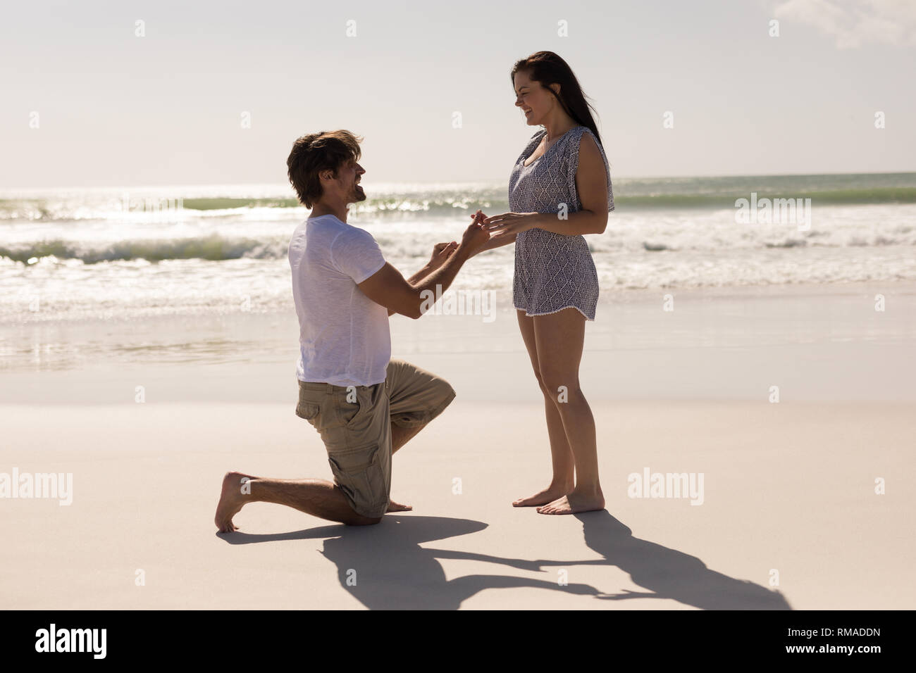 Romantic young man proposing to a woman on his knee Stock Photo