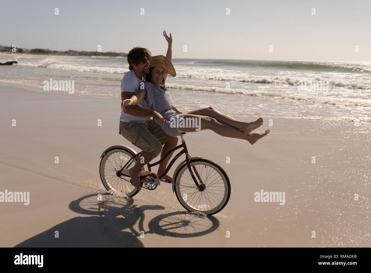 Beautiful happy young woman sitting on man bicycle handlebars - Stock Image