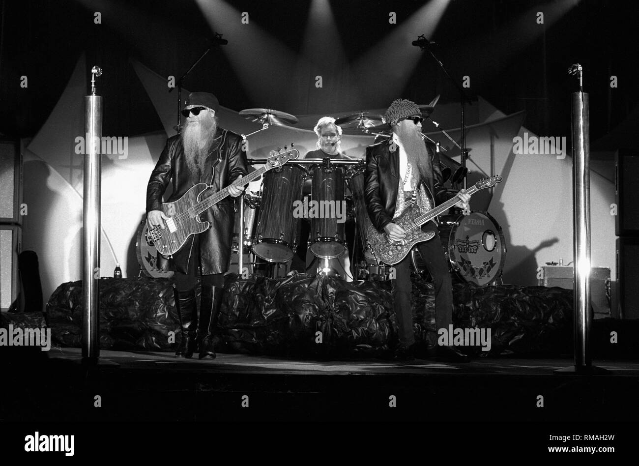 ZZ Top are shown performing on stage during a 'live' appearance. - Stock Image