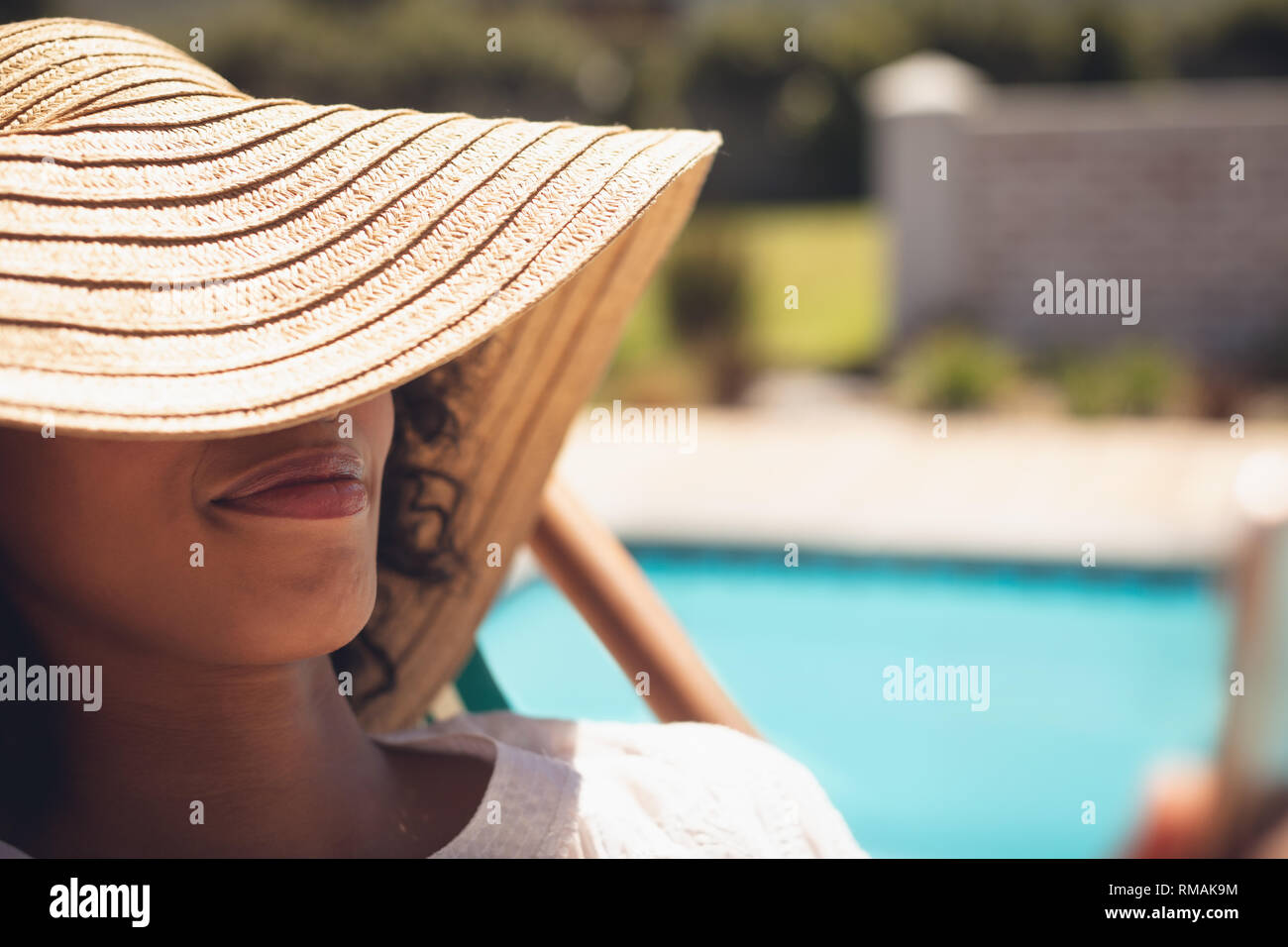 African American woman with hat relaxing on sun lounger in her backyard Stock Photo