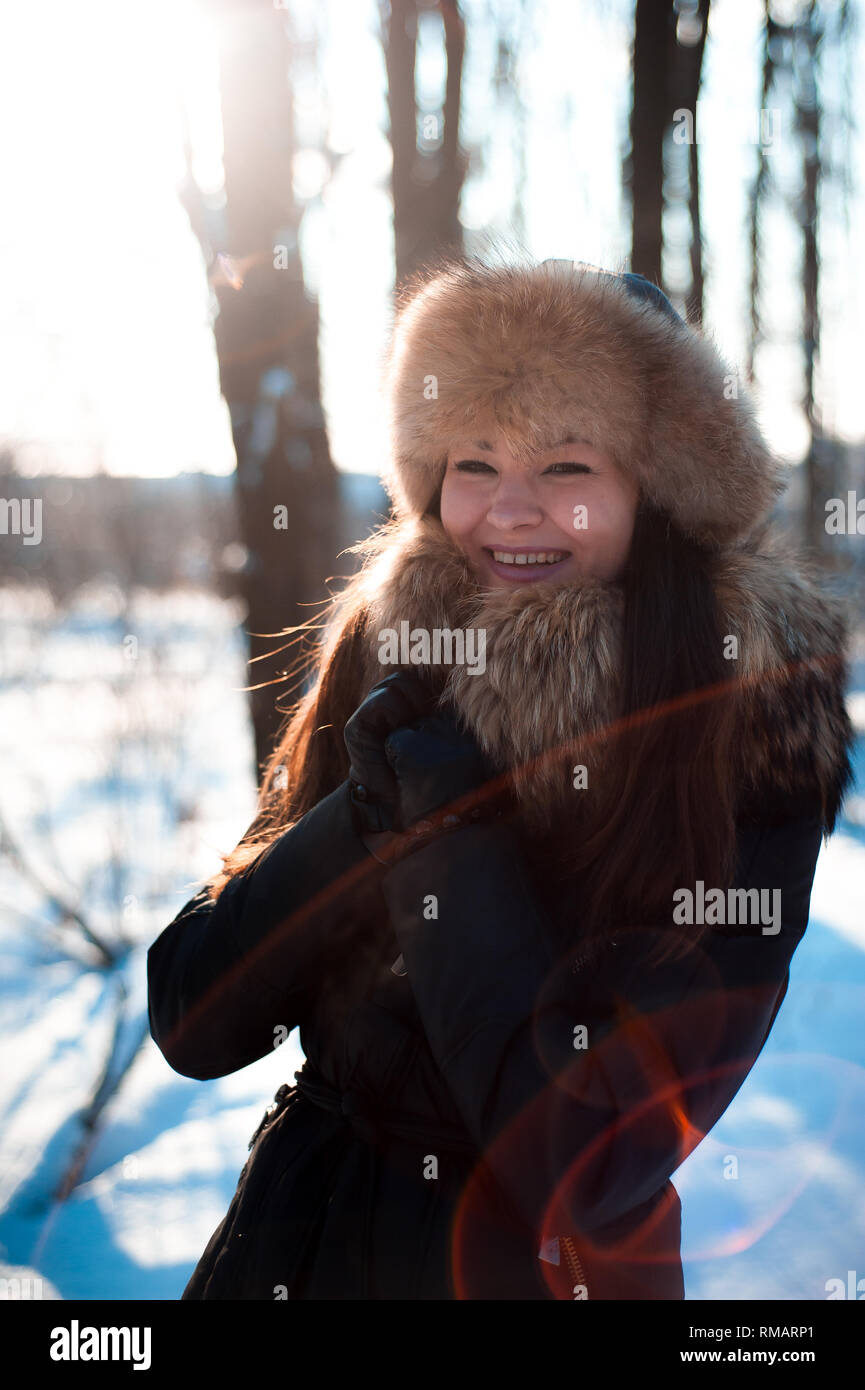 02fd2a5cc0afd girl in warm hat with ear flaps on the background of snow Stock ...