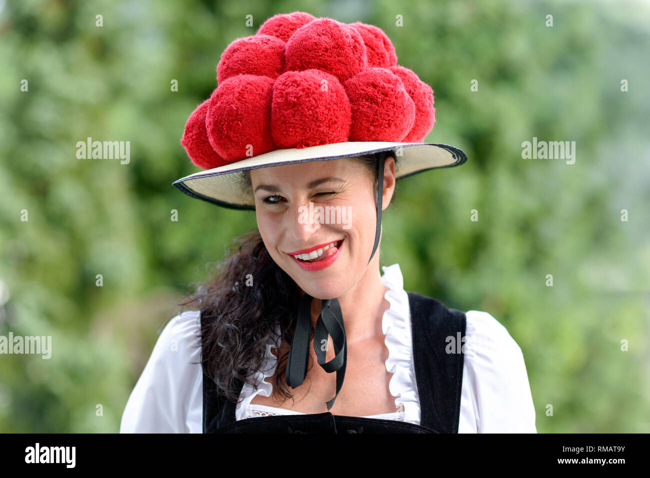 A portrait of a beautiful german woman wearing traditional clothing and a bollenhut licking her teeth. - Stock Image