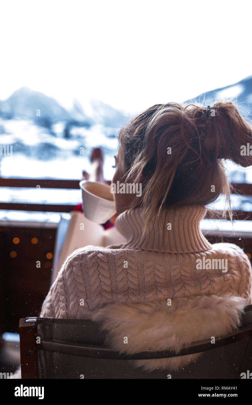 76c43c090e67 Young beautiful lady in cozy pajama sitting outdoor on the terrace and  drinking coffee.Panoramic view from the hotel on the winter Switzerland  mountai
