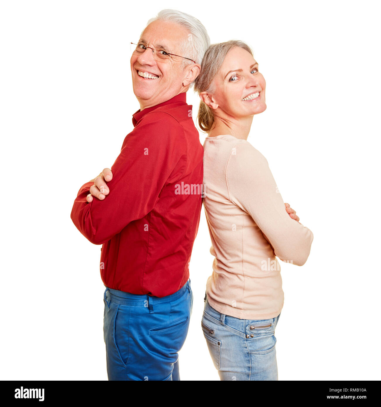 Happy seniors couple leaning back to back with crossed arms - Stock Image