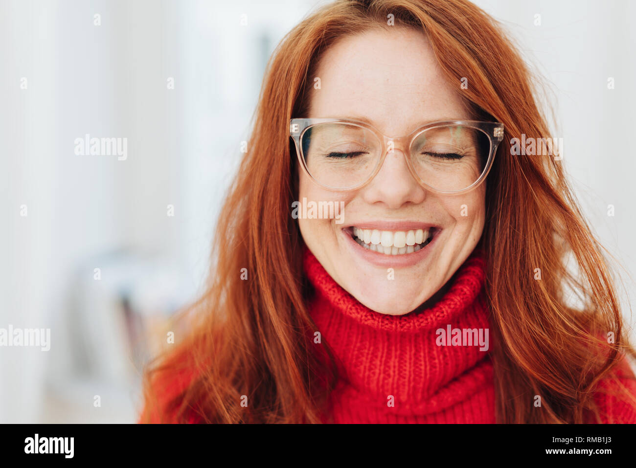 Pretty young woman wearing glasses beaming at the camera with a toothy grin as she closes her eyes - Stock Image