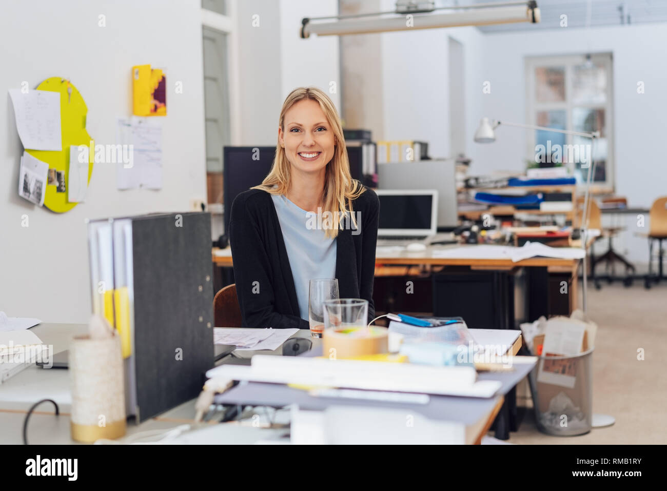 Happy young woman portrait sitting at the desk, alone in open space office interior, smiling and looking at camera. Messy desk workplace with document - Stock Image