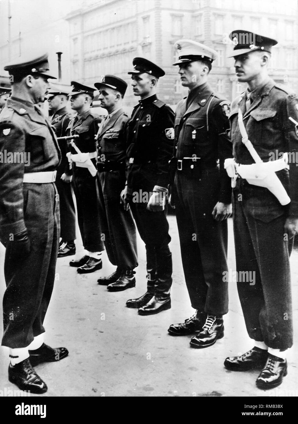 The international sector of Vienna is controlled by an international police force made up of all four occupying powers. An American, British, French and Russian military policeman form a patrol, and the superiors appoint a different occupation force regularly every month. Here, British Major Georges D. Pillitz, deployed at this moment as a watch commander, calls together a morning assembly. - Stock Image