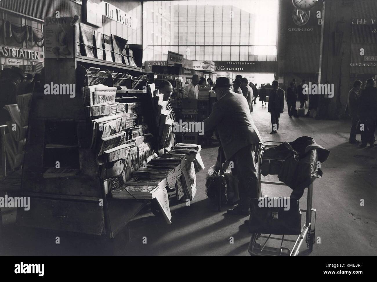 Series of the historical Muenchen Hauptbahnhof, October 1971. Trading at the station, newsdealer with a customer during shopping. Stock Photo