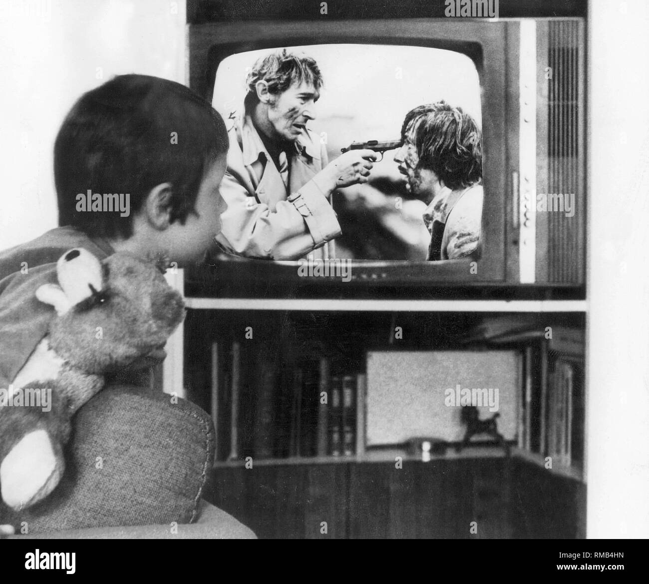 Children watch TV: Brutality and crime on German television, 1972. Five-year-old Ralf watches TV and clings to his teddy. The program shows a scene from the 'Tatort' crime movie 'Rattennest'. - Stock Image